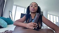 Brit black female with curly hair and ponytails, Olivia is fellating a ample, dark-hued meat stick