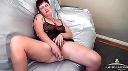 Thick babe on a satin sheet fucks a dildo
